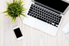 Tavola della scrivania con il computer portatile ed il fiore Fotografia Stock