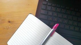 Tavola della scrivania con il computer portatile ed il taccuino Immagini Stock