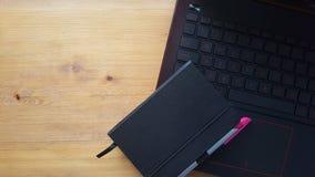 Tavola della scrivania con il computer portatile ed il taccuino Immagine Stock Libera da Diritti