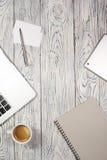 Tavola della scrivania con il computer portatile, il blocco note, la penna ed altra rifornimenti Immagine Stock