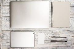 Tavola della scrivania con il computer portatile, il blocco note, la penna ed altra rifornimenti Fotografia Stock Libera da Diritti