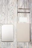 Tavola della scrivania con il computer portatile, il blocco note, la penna ed altra rifornimenti Immagini Stock