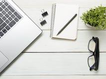 Tavola della scrivania con il computer, rifornimenti, fiore Vista superiore Copi lo spazio per testo Immagine Stock