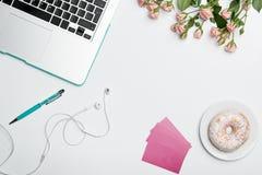 Tavola della scrivania con il computer, rifornimenti, fiori Fotografie Stock Libere da Diritti