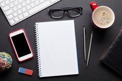 Tavola della scrivania con il pc, il blocco note, i vetri, il caffè ed il telefono Immagine Stock