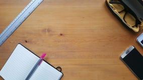 Tavola della scrivania con il telefono, il righello ed il taccuino Immagini Stock