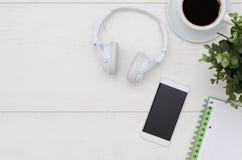 Tavola della scrivania con il telefono, le cuffie ed i rifornimenti Fotografie Stock Libere da Diritti