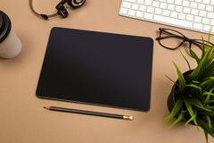 Tavola della scrivania con le cuffie caffè e vetri della tastiera della compressa falsi sul modello Vista superiore fotografia stock
