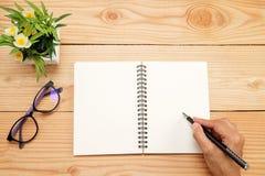 Tavola della scrivania con lo smartphone, penna sul taccuino, tazza di coffe Fotografie Stock