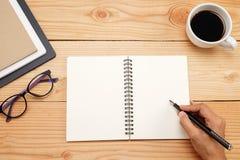 Tavola della scrivania con lo smartphone, penna sul taccuino, tazza di coffe Immagine Stock