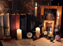 Tavola della strega con gli oggetti magici, le candele e le vecchie pergamene mistiche Fotografie Stock