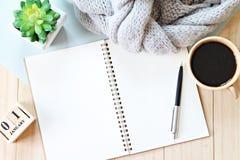 Tavola dello scrittorio con la sciarpa, la carta del taccuino, il calendario del cubo e la tazza di caffè immagini stock