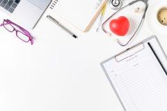 Tavola dello scrittorio di medico con lo stetoscopio ed il cuore rosso fotografie stock