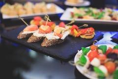 Tavola di banchetto d'approvvigionamento meravigliosamente decorata con differenti spuntini ed aperitivi dell'alimento Immagini Stock