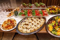 Tavola di banchetto d'approvvigionamento meravigliosamente decorata con differenti spuntini ed aperitivi dell'alimento su corpora immagine stock libera da diritti
