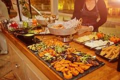 Tavola di banchetto d'approvvigionamento meravigliosamente decorata con i piatti ed il contorno caldi differenti dell'alimento di immagine stock