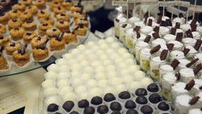Tavola di banchetto e presentato vari piccoli dolci, caramelle, bianco e cioccolato fondente e un vetro con del dessert stock footage