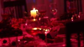 Tavola di banchetto in un ristorante con i vetri e una candela, un vetro con vino rosso e bianco su una tavola di banchetto sulla archivi video