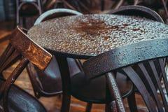 Tavola di Brown con le sedie in tempo piovoso su un terrazzo del ristorante Immagini Stock Libere da Diritti