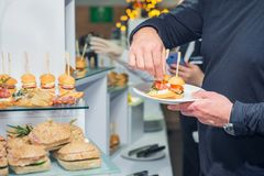 Tavola di buffet di approvvigionamento con alimento e gli spuntini per gli ospiti dell'evento Gruppo di persone in tutti che poss fotografie stock