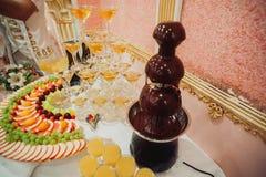 Tavola di buffet con una cascata della fontana del cioccolato e del champagne Fotografie Stock Libere da Diritti