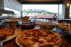 Tavola di buffet greca della prima colazione in pieno con le varietà di alimento con la priorità alta della pizza e di vista dell Immagini Stock