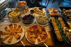 Tavola di buffet greca della prima colazione in pieno con le varietà di pizza, di torte, di pasta, di barbabietola, di insalate d Immagini Stock