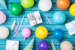 Tavola di compleanno del partito Palloni variopinti, regali, coriandoli e cappuccio di carnevale sulla vista blu del piano d'appo immagini stock