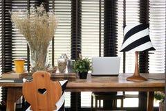 Tavola di funzionamento di legno con un computer portatile, una lampada d'annata e un cuscino Immagini Stock