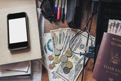 Tavola di funzionamento sudicia, con contanti, il passaporto, lo smartphone, il computer portatile ed ecc immagini stock