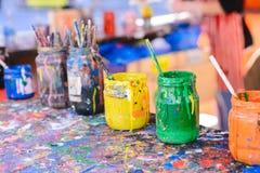 Tavola di lavoro di un decoratore delle terraglie con differenti contenitori e pennelli di colore fotografia stock libera da diritti