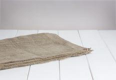 Tavola di legno bianca con la tovaglia, fondo leggero per il montaggio del prodotto fotografia stock