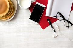 Tavola di legno con i pancake, tazza di latte, vetri, telefono, cuffie, nota Fotografie Stock