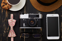 Tavola di legno con il cappello, macchina fotografica antiquata, occhiali, floreali Fotografia Stock