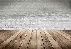 Tavola di legno con il fondo bianco del muro di mattoni Immagine Stock