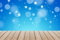 Tavola di legno con il fondo blu di colore con bokeh Immagini Stock Libere da Diritti