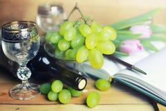 Tavola di legno con il libro e l'uva della bottiglia di vino Immagini Stock
