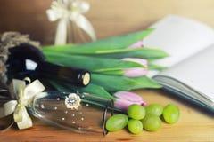 Tavola di legno con il libro e l'uva della bottiglia di vino Fotografia Stock