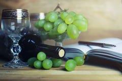 Tavola di legno con il libro e l'uva della bottiglia di vino Fotografie Stock