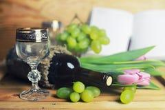 Tavola di legno con il libro e l'uva della bottiglia di vino Immagine Stock