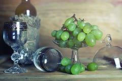 Tavola di legno con il libro e l'uva della bottiglia di vino Fotografie Stock Libere da Diritti