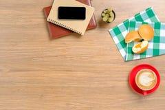 Tavola di legno con il taccuino, smartphone Fotografia Stock Libera da Diritti
