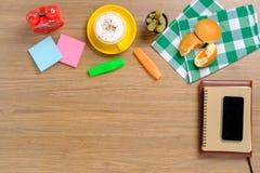 Tavola di legno con il taccuino, smartphone Fotografia Stock