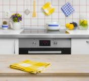 Tavola di legno con il tovagliolo giallo sul fondo della cucina Fotografie Stock Libere da Diritti