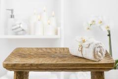 Tavola di legno con l'asciugamano della stazione termale sul fondo vago dello scaffale del bagno immagini stock