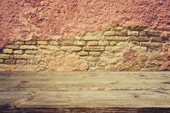 Tavola di legno d'annata vuota sopra il vecchio muro di mattoni immagine stock
