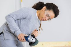 Tavola di legno d'insabbiamento della donna con la sabbiatrice elettrica Fotografia Stock