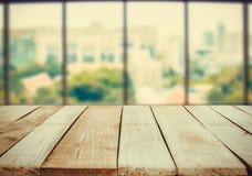 Tavola di legno davanti al fondo verde bianco della sfuocatura astratta dalla finestra dell'ufficio Fotografie Stock