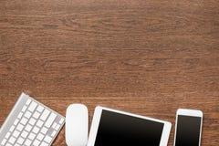 Tavola di legno dell'ufficio con la compressa, la tastiera, il topo e lo smartphone Fotografie Stock Libere da Diritti