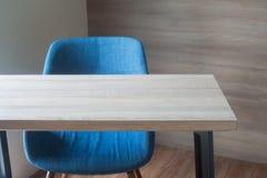Tavola di legno dell'ufficio con la sedia blu sul textur di legno del fondo della parete Fotografia Stock
